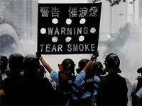 שוטר מזהיר מפגינים בעימותים בהונג קונג / צילום: Athit Perawongmetha, רויטרס