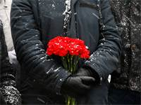 אישה מחזיקה פרחים בעצרת לזכרון השואה בגרמניה / REUTERS/Vasily Fedosenko
