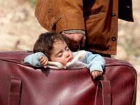 פעוט ישן במזוודה שנושא אביו בעת בריחתם מאזור קרבות בסוריה, מרץ 2018 / צילום: רויטרס - Omar Sanadiki