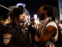 מפגין ושוטר במחאה על אלימות משטרתית אתמול / צילום: Corinna Kern, רויטרס