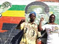 צעירים זימבבואים על רקע דיוקנו של מוגאבה לאחר היוודע הידיעות על מותו / צילום: רויטרס, PHILIMON BULAWAYO