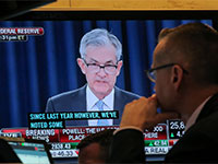 """פעיל בשוק צופה ביו""""ר הפדרל ריזרב, ג'רום פאוול / צילום: רויטרס - BRENDAN MCDERMID"""