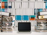 מחשב על רקע תיקיות / צילום: shutterstock