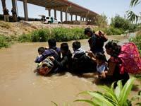 """מהגרים לא חוקיים מגואטמלה חוצים את נהר הריו בראבו שמפריד בין מקסיקו לארה""""ב/ צילום: רויטרס Jose Luis Gonzalez"""