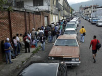 אנשים בתור לסופרמרקט וכלי רכב בתור לתחנת דלק בקרקאס /  צילום: רויטרס, Carlos Eduardo Ramirez