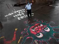 שוטר עומד בכביש שעליו מצויר ציור המעורר מודעות לנגיף הקורונה / צילום: Anupam Nath, AP