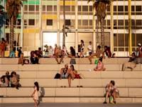 אנשים יושבים בטיילת בתל אביב ליד חוף הים בזמן גל חום / צילום: Oded Balilty, AP