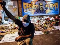 מפגין עומד על רקע קיר זכרון לנרצח פלויד ג'ורג' / צילום: John Minchillo, Associated Press