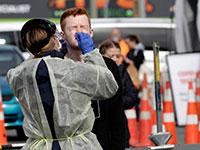 בדיקות קורונה נערכות בין הלקוחות הממתינים בתור לסופרים בניו זילנד. תוכנית ניהולית מקיפה וברורה שיושמה מהרגע הראשון / צילום: Mark Baker, Associated Press