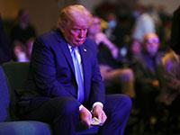 """הנשיא טראמפ סופר שטרות לפני שהוא תורם אותם לצדקה בתום אירוע תפילה ב""""כנסייה הבינלאומית"""" בלאס וגאס / צילום: Carlos Barria, רויטרס"""