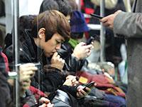 """מחוברים לניידים. """"עדיין לא רואים את ההשפעה הגורפת על החברה"""" / צילום: Ahn Young-joon, Associated Press"""