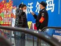 מאבטח בודק טמפרטורת גוף של אישה שרוצה להכנס למכולת / צילום: Mark Schiefelbein, Associated Press