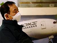 אחד הנוסעים הדרום קוריאנים שנדבקו בקורונה מחכים בשדה התעופה בן גוריון / צילום: Ariel Schalit, Associated Press
