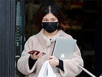 צעירה בבייג'ין יוצאת ממרכול בסין עם מסיכה בגלל נגיף הקורונה / צילום: Frank Augstein , Associated Press