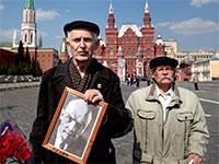 תומכי לנין עם תמונה של לנין בכיכר האדומה, מוסקבה / צילום: Alexander Zemlianichenko, Associated Press