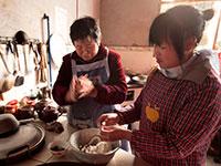 מבשלים בבית במחוז אנחווי שבסין / צילום: Yao Dawei, Associated Press