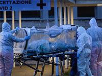 אנשי צוות רפואיים מובילים חולה קורונה לבית חולים ברומא בחליפות מגן / צילום: Associated Press