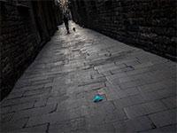 מסיכת מגן זרוקה על מרצפות אחת הסמטאות העמוסות של העיר העתיקה בברצלונה. כעת ריקה / צילום: Emilio Morenatti, Associated Press