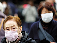 אישה מבוגרת הולכת עם מסיכה בתוך קהל של אנשים. ההנחה היא שרוב החולים יפתחו נוגדנים / צילום: Eugene Hoshiko, Associated Press