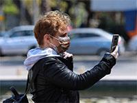 צעיר עם מסיכה ועם הטלפון שלו בתל אביב / צילום: שלומי יוסף, גלובס