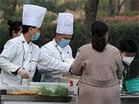 צוות של מסעדה בבייג'ינג מוכר ארוחות מחוץ לחנות, ביום רביעי השבוע / צילום: רויטרס