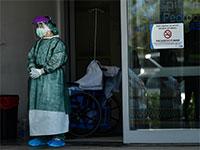 רופאה, מצויידת בחליפת מגן ומסיכה, ממתינה במפתן הדלת, לחולה קורונה הבא שעומד להגיע  / צילום: Alvaro Barrientos, Associated Press