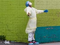רופא מהצוות הרפואי יוצא לשאוף אויר מתוך מחלקות הטיפול הנמרץ בבית החולים בברונקס, ניו יורק. הוירוס פוגע בשכבות החלשות יותר של האוכלוסיה בגלל המחסור באמצעים. / צילום: Mary Altaffer, Associated Press