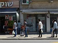 שומרים על מרחק בטוח בתור למכולת שכונתית בצל הקורונה / צילום: איל יצהר, גלובס