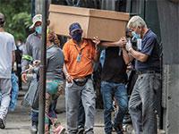 אזרחי אקוודור נושאים ארון קבורה מקרטון בדרך לבית קברות בגוואייאקיל / צילום: Luis Perez, Associated Press