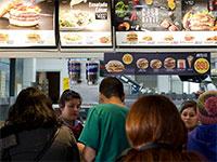 עומדים בתור לקניית מזון מהיר מול המסכים הצבעוניים עליהם מרצד התפריט / צילום: Esteban Felix, Associated Press