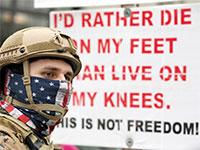 """מפגין עם אפוד ונשק בניו המפשייר בסוף השבוע. """"אני מעדיף למות על רגליי מאשר לחיות על ברכיי - זו לא חירות!"""", נכתב על השלטים / צילום: Michael Dwyer, Associated Press"""