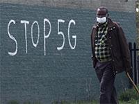 אדם עם מסכה בלונדון, על רקע גרפיטי נגד רשתות 5G  / צילום: RUSSELL BOYCE, רויטרס