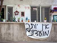 שלט תלוי מעל אחת המרפסות בתל אביב באוירת הסגר שהוטל על המדינה בעקבות התפשטות וירוס הקורונה / צילום: כדיה לוי, גלובס
