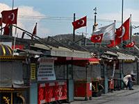 בעל חנות יושב מחוץ לחנות הסגורה שלו בשדרת קניות נטושה באיסטנבול, תורכיה. הסגר גרם לאבטלה חמורה שבין היתר גורמת ללירה התורכית להגיע לשפל חדש / צילום: Emrah Gurel, AP