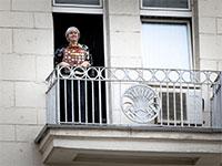 אישה מחזיקה מחוץ למרפסת מדליות של בני משפחתה בדקת דומיה לכבוד הנצחון של הצבא האדום על הנאצים, מוסקבה / צילום: Alexander Zemlianichenko, Associated Press