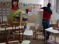 הורה מסדר אזור ישיבה לפי כללי הישיבה החדשים טרם כניסת התלמידים לכיתה / צילום: Sebastian Scheiner, Associated Press