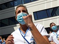 """הצוותים הרפואיים בבלגיה יוצאים במחאה על תנאי העסקתם, בזמן שראשת הממשלה מגיעה לבקר. על המסיכות הכיתוב """"take care of the care"""" / צילום: Yves Herman, רויטרס"""