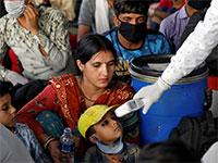 מדידות חום למניעת התפשטות קורונה, בתחנת רכבת באחמדאבאד שבהודו  / צילום: Amit Dave, רויטרס