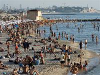 ישראלים מבלים על חוף הים בתל אביב, החודש / צילום: Amir Cohen, רויטרס