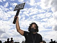 מפגין מחזיק שלט שנושא את המילים שמהדהדות את המחאה על רצח ג'ורג' פלויד / צילום: Associated Press