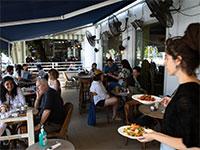 מלצרית מגישה מנות לסועדים בבית קפה בתל אביב / צילום: Sebastian Scheiner, Associated Press