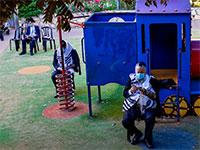 מתפללים בגן שעשועים בעקבות האיסור ולהתקהל ולהתפלל בבתי כנסת / צילום: Oded Balilty, Associated Press