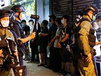 המשטרה עוצרת מפגינים פרו־דמוקרטים בהונג קונג, בשבוע שעבר / צילום: TYRONE SI, רויטרס