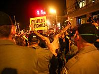 מפגין מסמן עצור בהפגנה בבלפור / צילום: Oded Balilty, Associated Press