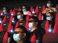 צופים בבייג'ינג, השבוע. בתי הקולנוע מורשים למלא עד 30% מהאולם  / צילום: Mark Schiefelbein, Associated Press