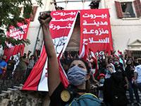 """מפגינים מול משרד החוץ בביירות, שנפרץ ביום שבת. על השלטים: """"ביירות בירת המהפכה"""" / צילום: Bilal Hussein, Associated Press"""