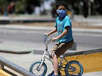 ילד עם מסכה רוכב לבד על האופניים בימי קורונה / צילום: Manaure Quintero, רויטרס