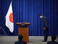 ראש ממשלת יפן, שינזו אבה, קד קידה לדגל יפן לפני תחילת מסיבת העיתונאים, שבה הודיע על פרישתו ביום שישי / צילום: Franck Robichon, Associated Press