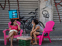 צעירים יושבים מחוץ לבית קפה שנפרס לרחוב על רקע העסקים הסגורים בשעת יום / צילום: כדיה לוי, גלובס