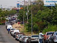 אנשים ממתינים בתור בניסיון לתדלק את מכוניותיהם בתחנת דלק במרקאיבו, ונצואלה, 2019 / צילום: Isaac Urrutia, רויטרס
